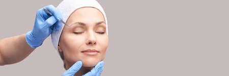 Beautician skin care. Face tweezers. Facial treatment. Woman dermatology. Salon routine. Applying mascara with device. Doctor procedure. Eyebrow countour tint. Beauty hair concept. Banner. Copyspace Standard-Bild
