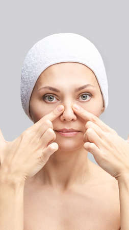Pretty woman do self face massage. Grey background. Beauty female portrait. Hands near nose. Medical diagnostic. Skin care cosmetology procedure. Natural mask. Cosmetics product. Foto de archivo