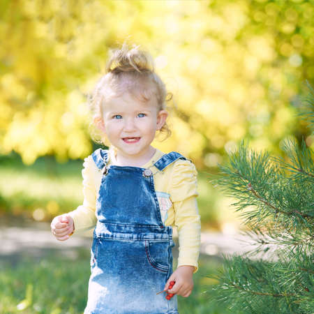 Beautiful little girl smiling. Look not at the camera. Park outside the house. Advertising photo. Positive child after quarantine. End lockdown