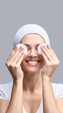 Cosmetology face cleaning. Female beautiful portrait. White cotton pad. Home facial routine. Remove make up. Demakeup toner. Foundation sponge. Cosmetics product. Grey background