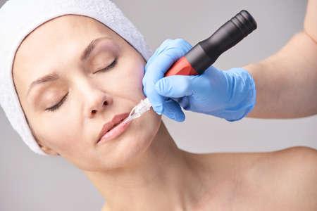 Beautician skin care. Face permanent make up. Facial treatment. Woman dermatology doctor. Applying tattoo mascara with device. Salon procedure. Lip countour tint. Medical concept.
