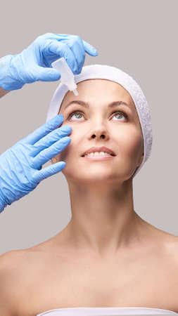 Girl with eye drops. Doctor hands applying eyewash. Foto de archivo