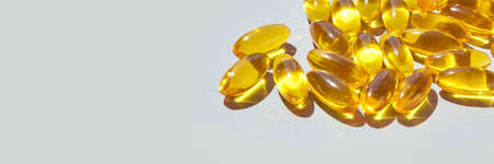 Omega3 gel capsule. Sun shadow. Yellow vitamin. Foto de archivo