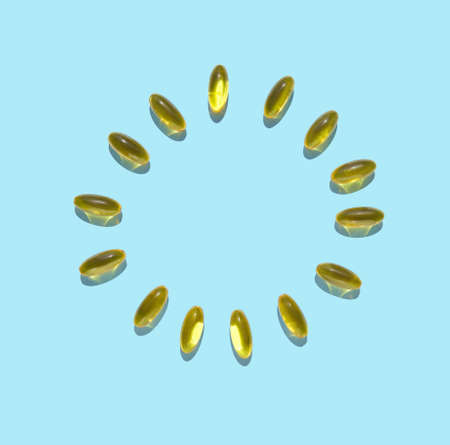 Omega3 gel capsule. Yellow vitamin. Health eating. Dietology drug. Fish oil supplement. Cirlce concept. Golden color softgel collagen. Blue background. Medicine immunity cosmetics Foto de archivo