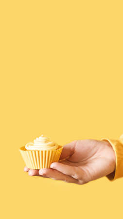 Yellow monochrome bakery. Sustainable cupcake cup. Hold in hand. Gold maffin cream. Trendy colourful desert. Bright birthday gift. Vertical banner for story. Copyspace Foto de archivo