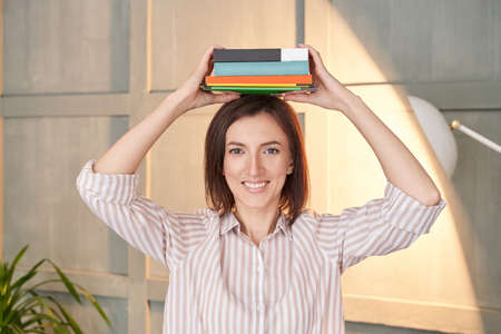 Univetsity research. Pretty woman working at home. Portrait with books on head. Indoors office. Learning language. Female human lifestyle. Student eyes. Education concept. Lockdown lessons