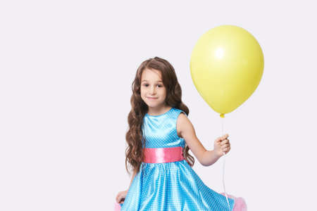 Celebration. Girl portrait. Happy child. Person hold yellow air balloon. Blue Dress. Look at camera. Pretty kid. Summer party. White background. Lady face