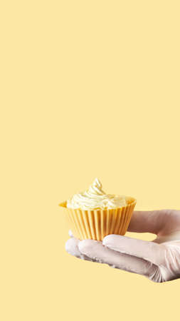 Yellow monochrome bakery. Sustainable cupcake cup. Hold in hand. Gold maffin cream. Trendy colourful desert. Bright birthday gift. Vertical banner for story. Copyspace. Protective glove