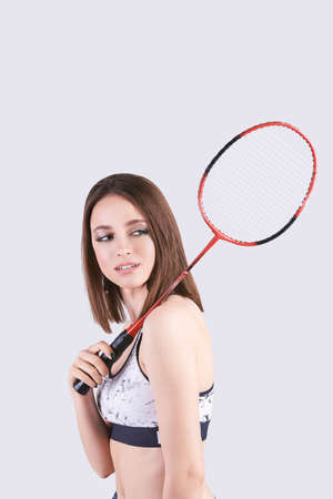 Beauty sport. Pretty young woman in fitness clothes. Slim body. Look at camera. Badminton exercise. Power wellness. Workout lifestyle. Training position. Grey isolated background Foto de archivo