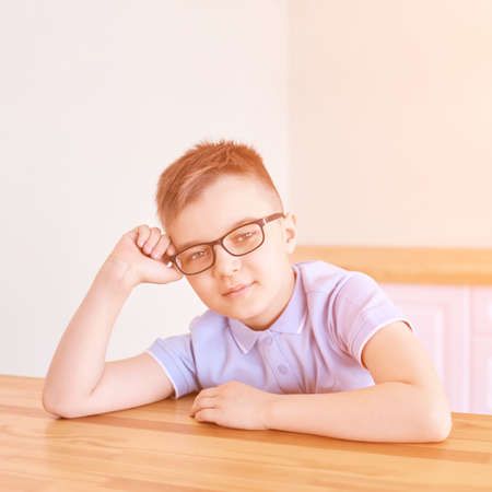 Little boy in eyeglasses thinking at home. Schoolboy study. Male child nerd. Young myopia. Student do homework. Online education. Light interior. Dreaming person