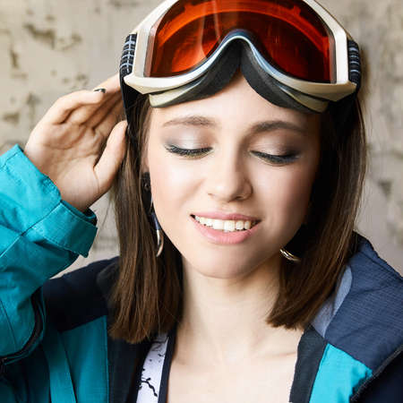 Beauty sport girl. Snowboard jacket. Pretty young woman in fitness clothes. Art makeup. Slim body. Health exercise. Power wellness. Workout lifestyle. Training position. Grey isolated background