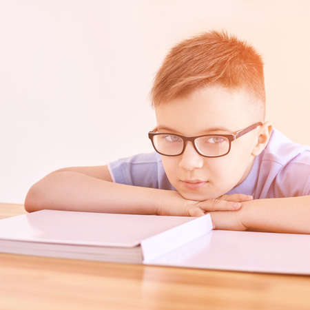 Little boy in eyeglasses thinking at home. Schoolboy study. Male child nerd. Young myopia. Student do homework. Online education. Light interior. Dreaming person. Book