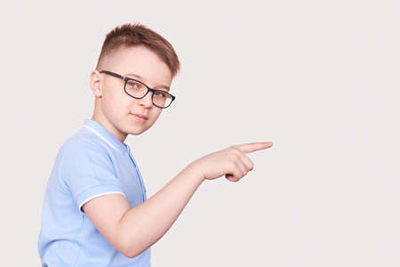 Smart schoolboy in eyeglasses. Boy wear specs. Funny little people. Pretty young student pointing. Elementary school children. Grey background. Child gesturing. Preschool learning. Male clever teacher