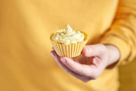 Yellow monochrome bakery. Sustainable cupcake cup. Hold in hand. Gold maffin cream. Trendy colourful desert. Bright birthday gift