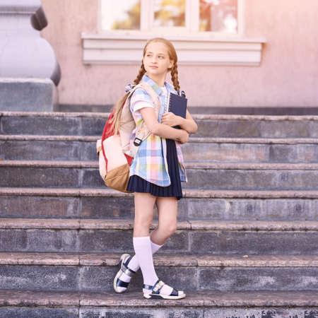Young schoolgirl with backpack. Lifestyle going to classroom. Outdoor autumn park. Children learn smart. Street student. Happy preschool kid. Back to school. Near building