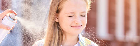 Beautiful american portrait of girl. Hairsprair at sun. Styling outdoors. Product bottle. Little female child. Haircut fixation. White caucasian kid. People creative work. Closed eyes