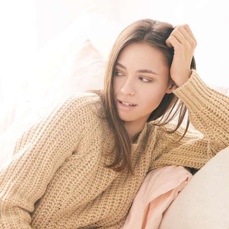 Beautiful young woman sitting on couch. Lifestyle portrait. Single female person. Home interior. Monochrome beige colors. Looking side. House room. Lockdown lazy day. Comfort time. Mortgage concept