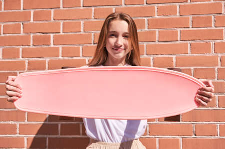 Young woman show skateboard deck. Pink mockup. Sun shade. High quality photo. Skatepark equipment. Teenagers lifestyle action. Street girl portrait. Extreme sport. Copyspace. Place for text