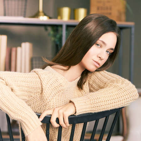 Beautiful young woman sitting on chair. Lifestyle portrait. Single female person. Home interior. Monochrome beige colors. Looking side. House room. Lockdown lazy day. Comfort time. Mortgage concept
