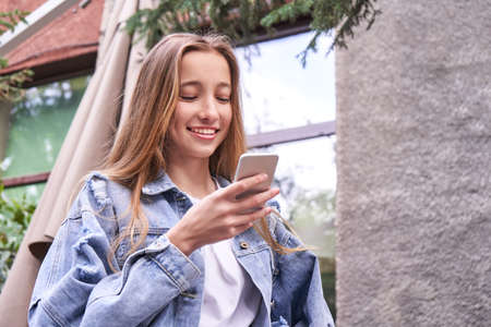 Smiling girl portrait. Holding smartphone. Outdoor view. Busy young woman text to her friend. Student lifestyle. Online education. Happy adult typing. Social media worker. Businesswoman. People chat