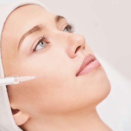 Cheek injection at spa salon. Doctor hands. Closeup view. High quality. Pretty female patient. Beauty treatment. Healthy skin procedure. Young woman face. Light background. Plasmolifting rejuvenation