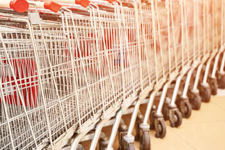 Retro shop trolley. Supermarket shopper. Grocery empty detail. Lots red basket at mall. Market interior. Discount marketplace. Many metal wheel at parking. Selective focus. Copyspace. Nobody