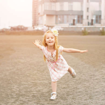 Baby girl funny posing. Outdoors female portrait. High quality photo. Autumn city activity. Lifestyle childhood. Caucasian person. Smile face. Little child joy expression. Copyspace