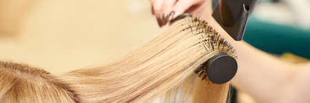 Repair long hair procedure. Haircut at salon. Woman hairstyle. Master hand with brush and fan. Adult female person. Closeup view. Studio equipment. Lady preparation. Blonde dry. Copyspace 写真素材