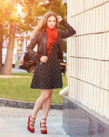 Young woman standing near wall. Outdoor female portrait. Business people outdoors. Red scarf. Bright dress. Log hair. Office manager. Attractive student in jacket. Copyspace. Standing. Red shoes 写真素材