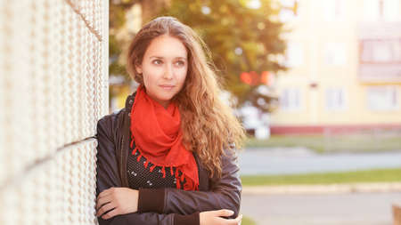 Young woman standing near wall. Outdoor female portrait. Business people outdoors. Red scarf. Bright dress. Log hair. Office manager. Attractive student in jacket. Copyspace