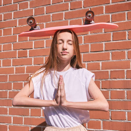 Young woman show skateboard deck. Pink color. Sun shade. High quality photo. Skatepark equipment. Teenagers lifestyle action. Street girl portrait. Extreme sport. Copyspace. Place for text