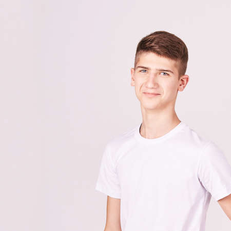 Teenager portrait. Young male person at studio. Look at camera. White t-shirt. High quality photo. Smart student boy. Smiling hipster. Hispanic Latin people. Copyspace. Attractive haircut