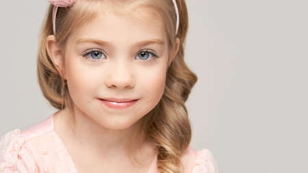 Little pretty girl portrait. Studio shot. Cute kid face. High quality photo. Smiling children. Blond hair. Caucasian female people. Beauty head. Grey background. American healthy person. Pink dress