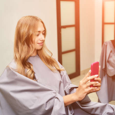 Long hair procedure at salon. Woman with smartphone. Adult female person. Studio equipment. Lady preparation. Copyspace. Barber therapy. Lifestyle selfie. Prom hairstyle. Bride service