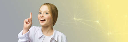 Pretty young girl portrait at studio. Blue eyes kid. Grey background. Child point up. Happy student. Model gesturing.