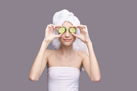 Young girl in studio. Bathroom towel. Cosmetology concept. Skin care product. Unrecognised female portrait. Cucumber face mask. Fruit scrub. Home peeling. Grey background. Copyspace