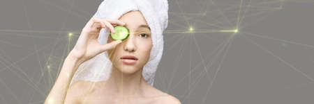 Young girl in studio. Bathroom towel. Cosmetology concept. Skin care product. Female portrait. Cucumber face mask. Fruit scrub. Home peeling. Grey background. Copyspace. Facial lifting treatment