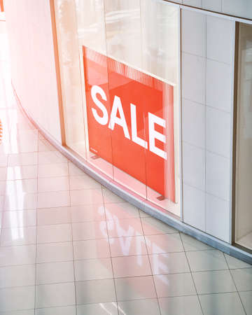 Sale red sign at mall. Discount concept. Market interior design. Selling business model. Lifestyle promotion. Store promo graphic. Shop background. Cheap boutique. Retail commercial price. Money offer 写真素材