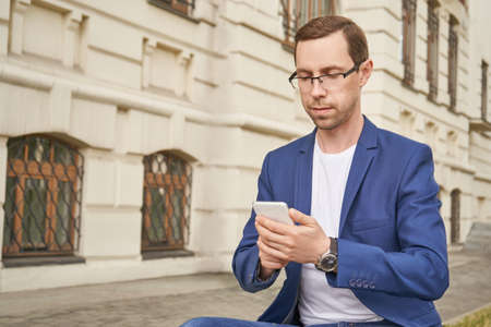 Man lifestyle at city. Male person portrait. Communication concept. Local travel. Using smartphone. Sms. Professional finance business. Smart student. Boy in eyeglasses