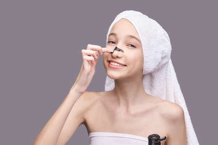 Young girl applying black mud face mask. 写真素材
