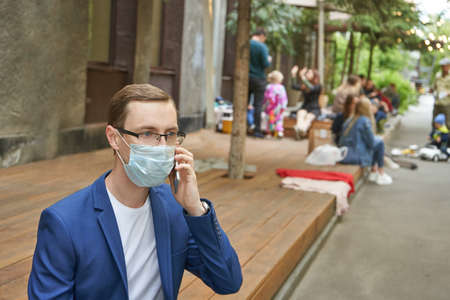 Man wear protective face mask and using smartphone.