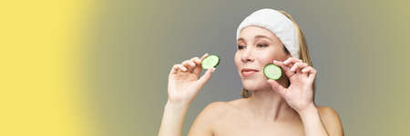 Young woman in studio. Bathroom towel. Cosmetology concept. Skin care product. Female portrait. Cucumber face mask. Fruit scrub. Home peeling. Grey background. Copyspace. Lifting treatment. Yellow