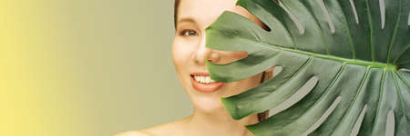 Young woman. Smiling with monstera leaf. Model at studio. Cosmetology health concept. Beautiful tropical leaf. Stomatology medical treatment. Female person happy portrait. Grey background. Copyspace