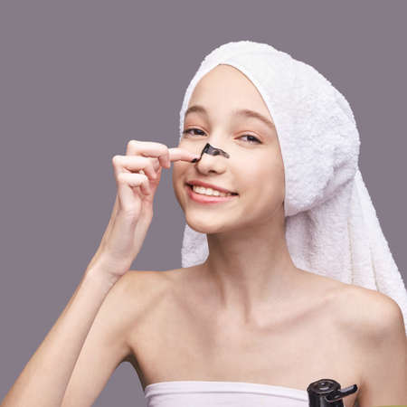Young girl in studio. Bathroom towel. Cosmetology concept. Skin care product. Female portrait. Black mud face mask. Home peeling. Grey background. Copyspace. Facial lifting treatment. Using charcoal