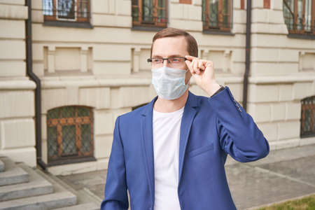 Man in protective face mask at city. Male person portrait. Lockdown concept. Sick communication. Allergy safety. Local travel. Respiratory prevention flu. Anti virus. Boy in eyeglasses