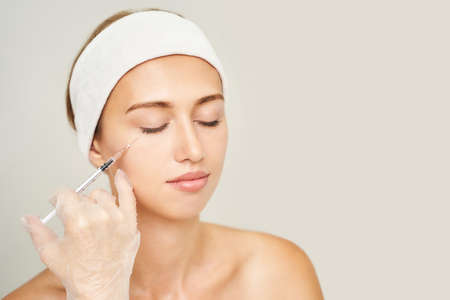 Cheek injection at spa salon. Doctor hands. Pretty female patient. Beauty treatment. Healthy skin procedure. Young woman face. Light background. Plasmolifting rejuvenation. Dermatology mask