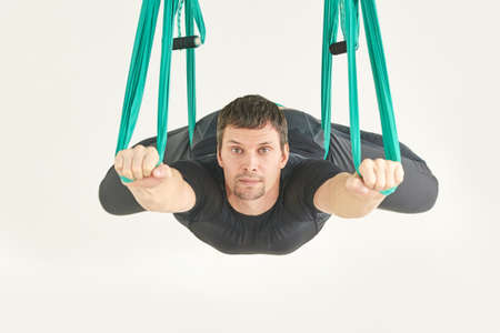 Male person do hammock yoga class exercise. Meditation in air calm. Aero beginner studio workout. Man lifestyle. Guy training zen pose. Green. Hammock stretching at gym