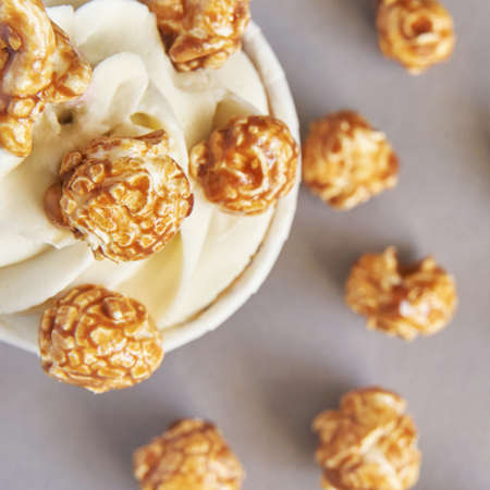 Milky cream cupcake. Birthday sweet bakery. Cookies. Yummy buttercream dessert. Wedding party food. Grey background. Holiday recipe. Anniversary gourmet. One pieces. Caramel popcorn