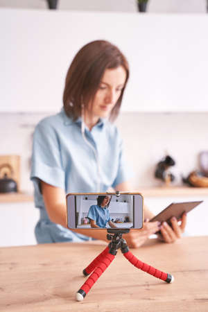 Young woman record video at kitchen. Self portrait in home. Blogger selfie video. Female person. Lifestyle action. Pretty posing. Lifestyle. Online study