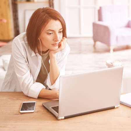 Young woman sitting at home. Working on notebook. Online study concept. Safety lockdown distance teaching. Female person. Quarantine office. Business writer. Фото со стока